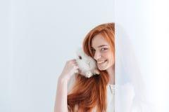 摆在用兔子的愉快的红头发人妇女 免版税库存图片