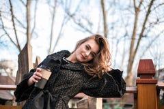 摆在用咖啡的美丽的少女室外 免版税图库摄影