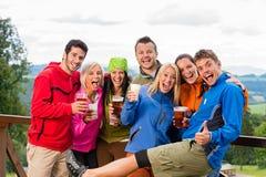 摆在微笑的青年人用啤酒户外 库存照片