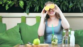 摆在用在眼睛的桔子的美女微笑和唬弄享用健康生活方式中景 影视素材