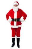 摆在用在腰部的现有量的快乐的圣诞老人 免版税库存照片