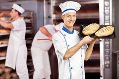 摆在用新近地被烘烤的面包的微笑的男性面包师在面包店 库存图片