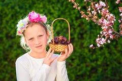 摆在用新鲜水果的逗人喜爱的女孩在晴朗的庭院里 有葡萄篮子的女孩  库存图片