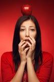 摆在用红色苹果的害怕的和被迷惑的学生女孩 免版税库存图片