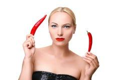 摆在用红辣椒的年轻白肤金发的妇女被隔绝 免版税库存图片