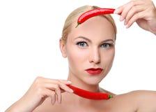 摆在用红辣椒的年轻白肤金发的妇女 免版税库存照片