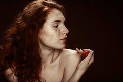 摆在用草莓的美丽的肉欲的裸体红头发人妇女 免版税库存图片