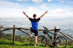 摆在用被举的手的男性骑自行车的人 库存照片