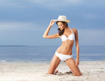 白色泳装的一名年轻深色的妇女在海滩 库存图片