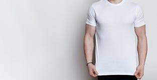 摆在白色背景的一个演播室的肌肉年轻人佩带的白色T恤杉一张水平的画象与空的空间 嘲笑 图库摄影