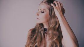 摆在白色背景的一个美丽的白肤金发的女孩的画象 股票视频