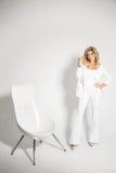 摆在白色背景的一套白色衣服的美丽的性感的金发碧眼的女人 免版税库存图片