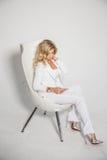 摆在白色背景的一套白色衣服的美丽的性感的金发碧眼的女人 库存照片