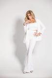 摆在白色背景的一套白色衣服的美丽的性感的金发碧眼的女人 库存图片