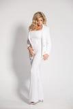 摆在白色背景的一套白色衣服的美丽的性感的金发碧眼的女人 免版税图库摄影