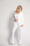 摆在白色背景的一套白色衣服的美丽的性感的金发碧眼的女人 免版税库存照片