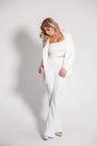 摆在白色背景的一套白色衣服的美丽的性感的金发碧眼的女人 图库摄影