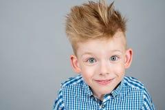 摆在白色背景的愉快,时兴的男孩画象  免版税库存照片