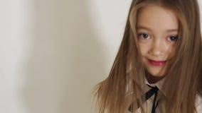 摆在白色背景的演播室的一件白色女衬衫的一个逗人喜爱的青少年的女孩 影视素材