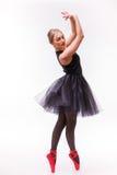 摆在白色芭蕾舞短裙和芭蕾舞鞋的女性芭蕾舞女演员在白色背景 免版税图库摄影