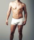 摆在白色裤子的年轻性感的人 免版税库存照片