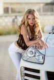摆在白色豪华车灯的美丽的白肤金发的少妇  免版税库存图片