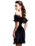 摆在白色backgr的演播室的黑礼服的年轻性感的妇女 免版税库存照片