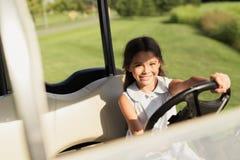 摆在的女孩拿着高尔夫球汽车的舵 库存照片