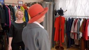 摆在的端庄的妇女微笑和,当适合红色帽子在时尚陈列室里时 选择典雅的帽子的时髦的成熟妇女  股票录像