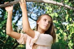摆在的迷人的女孩在夏天庭院里 免版税库存图片