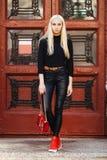 黑摆在的年轻时髦的运动的白肤金发的美丽的青少年的女孩反对葡萄酒红色门背景 青少年的都市城市成套装备 影片s 库存照片