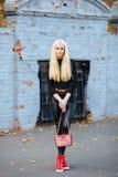 黑摆在的年轻时髦的运动的白肤金发的美丽的青少年的女孩在公园在反对老钴的一温暖的秋天天绘了砖墙b 库存照片