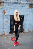 黑摆在的年轻时髦的运动的白肤金发的美丽的青少年的女孩在公园在反对老钴的一温暖的秋天天绘了砖墙b 库存图片