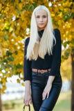 黑摆在的年轻时髦的运动的白肤金发的美丽的青少年的女孩在公园在反对被弄脏的黄色叶子backgrou的一温暖的秋天天 库存照片