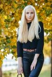 黑摆在的年轻时髦的运动的白肤金发的美丽的青少年的女孩在公园在反对被弄脏的黄色叶子backgrou的一温暖的秋天天 免版税库存照片
