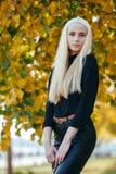 黑摆在的年轻时髦的运动的白肤金发的美丽的青少年的女孩在公园在反对被弄脏的黄色叶子backgrou的一温暖的秋天天 库存图片