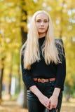 黑摆在的年轻时髦的运动的白肤金发的美丽的青少年的女孩在公园在反对被弄脏的黄色叶子ba的一温暖的金黄秋天天 库存图片