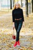 黑摆在的年轻时髦的运动的白肤金发的美丽的青少年的女孩在公园在反对被弄脏的黄色叶子ba的一温暖的金黄秋天天 图库摄影