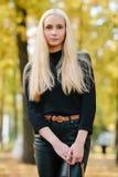 黑摆在的年轻时髦的运动的白肤金发的美丽的青少年的女孩在公园在反对被弄脏的黄色叶子ba的一温暖的金黄秋天天 库存照片