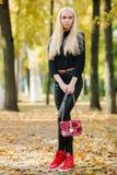 黑摆在的年轻时髦的运动的白肤金发的美丽的青少年的女孩在公园在反对被弄脏的黄色叶子ba的一温暖的金黄秋天天 免版税图库摄影