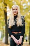 黑摆在的年轻时髦的运动的白肤金发的美丽的青少年的女孩在公园在反对被弄脏的黄色叶子ba的一温暖的金黄秋天天 免版税库存图片