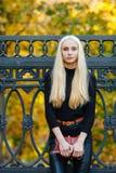 黑摆在的年轻时髦的运动的白肤金发的美丽的青少年的女孩在公园在反对铁篱芭的一温暖的金黄秋天天弄脏了黄色 库存照片