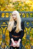 黑摆在的年轻时髦的运动的白肤金发的美丽的青少年的女孩在公园在反对铁篱芭的一温暖的金黄秋天天弄脏了黄色 免版税库存照片