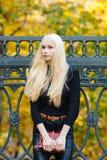 黑摆在的年轻时髦的运动的白肤金发的美丽的青少年的女孩在公园在反对铁篱芭的一温暖的金黄秋天天弄脏了黄色 库存图片