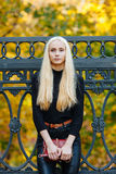 黑摆在的年轻时髦的运动的白肤金发的美丽的青少年的女孩在公园在反对铁篱芭的一温暖的金黄秋天天弄脏了黄色 免版税图库摄影