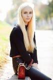 黑摆在的年轻时髦的运动的白肤金发的美丽的青少年的女孩在公园在反对阳光的一温暖的秋天天 青少年的都市城市成套装备 库存图片