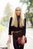 黑摆在的年轻时髦的运动的白肤金发的美丽的青少年的女孩在公园在反对阳光的一温暖的秋天天 青少年的都市城市成套装备 免版税库存图片