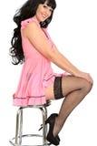 摆在相当有渔网长袜的桃红色女用贴身内衣裤的有吸引力的性感的闷热逗人喜爱的年轻模型 免版税库存照片