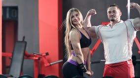 摆在看在健身房镜子的体型夫妇 库存照片