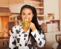 摆在睡衣和面对照相机的年轻深色的妇女,当愉快地时喝早晨茶 免版税库存图片